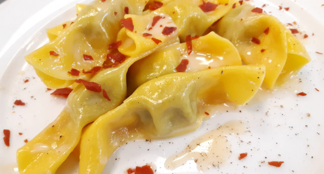 Candies shape pasta filled with nettle paste, parmigiano reggiano and crispy prosciutto