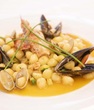 Chicche di patate con bisque e molluschi su letto di salsa di datterini gialli