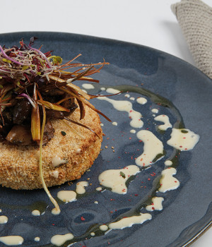 Crispy rice cake with truffle mushrooms and fried leeks