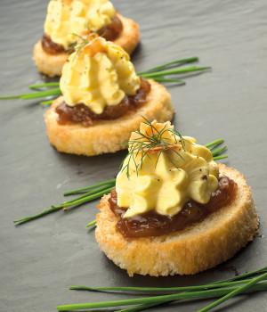 Geröstetes Brot mit Parmesanschaum, karamellisierten Zwiebeln und gerösteten Mandeln.