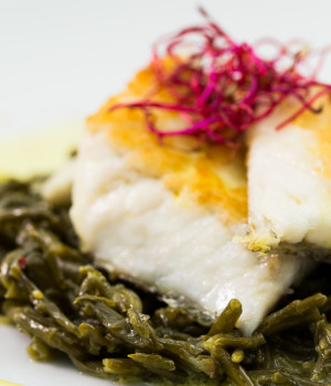 Darne of sea bass with saffron sauce served on a bed of samphire