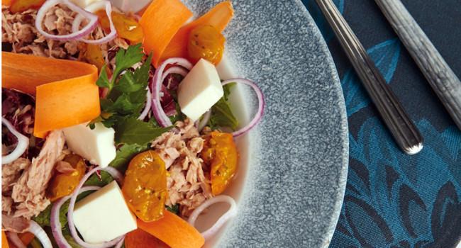 Ensalada de atún con tomates dátil amarillos, cebollas cortadas en rodajas y mozzarella