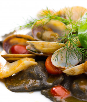 Squid ink perch Ravioli with clams, cuttlefish and cherry tomato