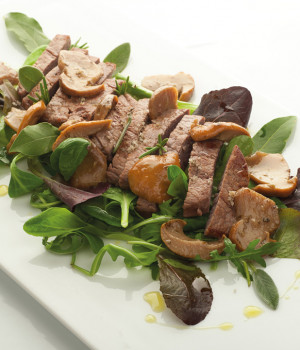 Beef tagliata with porcini mushrooms and mixed salad leaves